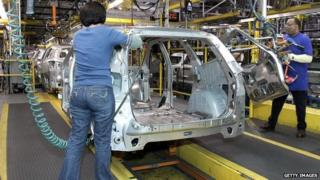 General Motors employees construct an SUV car in the Michigan plant