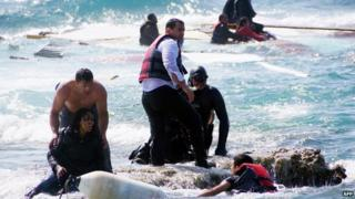 Local residents and rescue workers help a migrant woman after a boat carrying migrants sank off the island of Rhodes, southeastern Greece, 20 April 2015