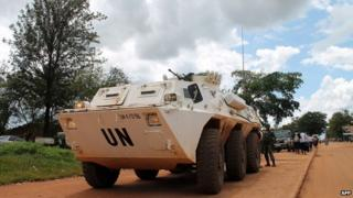 Poeple and blue helmet members of MONUSCO stand near a UN armoured vehicle