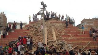 People stand around damage caused by an earthquake at Durbar Square in Kathmandu, Nepal, Saturday, April 25, 2015