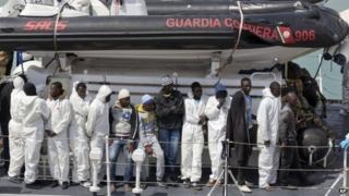 Migrants wait to disembark at Catania harbour, Sicily