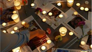 A woman places a flower on top of pictures of some of the prisoners to be executed in Indonesia during a vigil at Martin Place on 28 April 2015 in Sydney, Australia.
