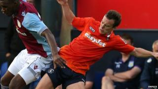 Shaun Whalley tackles Christian Benteke during Luton's pre-season friendly against Aston Villa