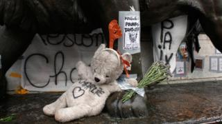 """Teddy bear with """"Charlie"""" written on it lays on the statue of the place de la Republique, three months after the terror attack against French satirical newspaper Charlie Hebdo"""