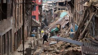 Man walks through rubble of houses damaged by the earthquake in Bhaktapur near Kathmandu on 28 April 2015.