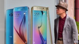 A man walks past a billboard showing the Samsung Galaxy S6 and S6 edge at a store in Seoul