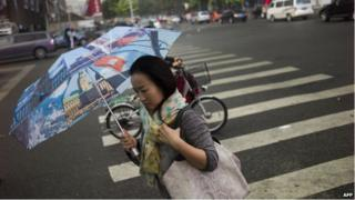 A woman protects herself from the rain with an umbrella in Beijing on 26 September 2014.