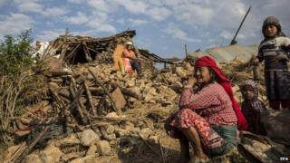 People in front of ruined home in Kathmandu, Nepal (27 April 2015)