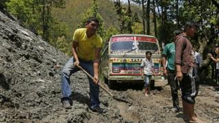 Bus driver digs mud from road in the Gorkha District of Nepal. 30 Apr 2015