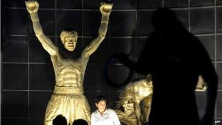 Fans of Philippine boxing superstar Manny Pacquiao pose for a picture by Pacquiao's statue at the bay side of Manila on November 26, 2010.