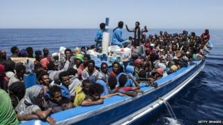 Migrants aboard a wooden boat on the Mediterranean sea