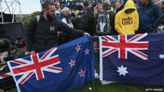 Visitors pack up New Zealand (L) and Australian flags at the conclusion of the Dawn Service at the Anzac Commemorative Site, which is the main event to commemorate Australian soldiers who died during the Gallipoli campaign, on the campaign's centenary on 25 April 2015 near Eceabat, Turkey.