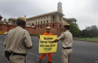 Indian policemen prepare to remove a Greenpeace activist as he holds a banner near the area of government offices and the Indian Parliament in New Delhi in 2012