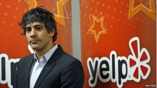 Jeremy Stoppelman in front of Yelp logo