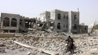 A man rides a motorcycle past a headquarters of the Houthi group, which was destroyed after an air strike by a Saudi-led coalition, in Saada, Yemen (April 26, 2015)