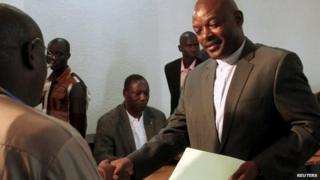 Burundian President Pierre Nkurunziza submits his documents as he registers to run for a third five-year term in office