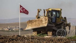 A Turkish army digger is parked next to a Turkish flag at the new site of the Suleyman Shah tomb in the northern Syrian village of Esmesi, Aleppo province, on 22 February 2015