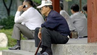 An elderly Korean man sitting alone on some steps