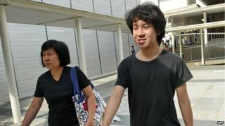 Amos Yee (R), a 16-year-old student, and his mother leave the State courts in Singapore on 31 March 2015