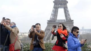 People taking selfies in front of the Eiffel Tower in Paris