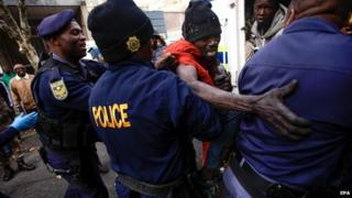Members of the South African Police detain a foreign national in downtown Johannesburg, South Africa, 08 May