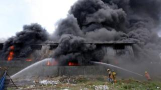 Firemen train their hoses at the burning Kentex footwear factory at Valenzuela city, a northern suburb in Manila, Philippines, Wednesday, May 13, 2015