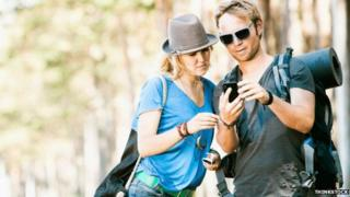 Couple on a trek using a mobile phone