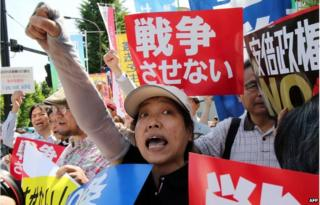 Activists shout slogans against Japanese Prime Minister Shinzo Abe as some 500 protestors gather in front of the prime minister's official residence in Tokyo on 14 May 2015.