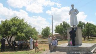 Villagers gathering around the Stalin statue