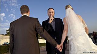Noel Biderman in between married couple