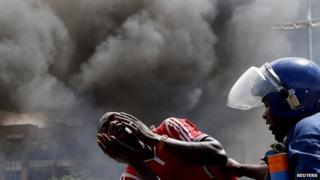 "A detained protester cries in front of a burning barricade during a protest against President Pierre Nkurunziza""s decision to run for a third term in Bujumbura, Burundi on 13 May 2015."