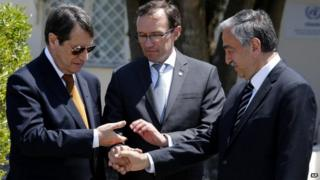President Nicos Anastasiades, left, Turkish Cypriot leader Mustafa Akinci, right, and United Nations envoy Espen Barth Eide shake hands after their talks at a UN compound inside the UN buffer zone at the abandoned Nicosia airport, in the Cypriot divided capital Nicosia on 15 May 2015