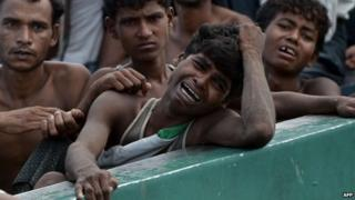 A Rohingya migrant crying as he sits with others in a boat drifting in Thai waters off the southern island of Koh Lipe in the Andaman, 14 May, 2015