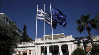 A Greek national flag and a European Union flag flutter