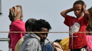 Migrants disembark from an Italian military ship as they arrive in the port of Augusta, on the eastern coast of Sicily (21 May 2015)