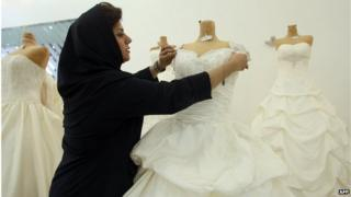 Woman adjusts a wedding dress in a shop in tehran (file photo)