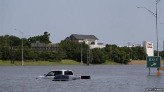 A car floating in water off of a highway in Texas