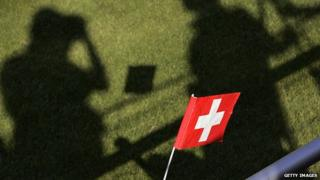 A young Switzerland supporter waves a flag as shadows of media representative are seen prior to the first training of the Switzerland's football team in 2006