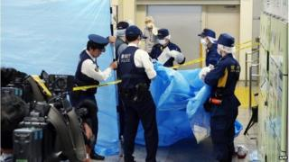Police inspect a locker at Tokyo station (31 May 2016)
