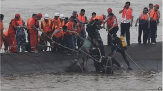 Rescuers help a woman to safety from the upturned boat (2 June 2015)