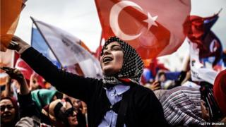 A woman supporting Turkish Prime Minister Recep Tayyip Erdogan cheers and wave Turkish and AK Party (AKP) flag during an election rally in Istanbul on March 23, 2014