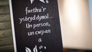 Un o arwyddion siop goffi rhyngwladol yn Aberystwyth