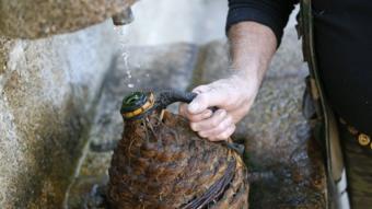 رجل يملأ زجاجة من صنبور مياه ضعيفة