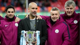 غوارديولا يحمل كأس البطولة مع أعضاء الجهاز الفني