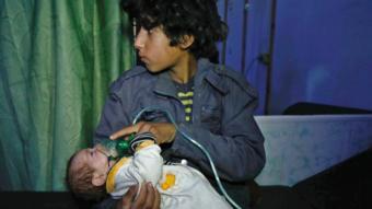 طفل يحمل رضيع ويضع له قناع أكسجين، في هجوم بالغاز على دوما في يناير/كانون الثاني 2018