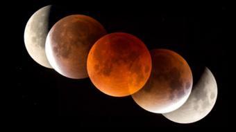 القمر يبدو باللون الأحمر أثناء الخسوف يتلاشى ضوء الشمس أثنار رحلته نحو الغلاف الجوي للأرض
