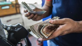 عامل في محطة وقود يعد نقود