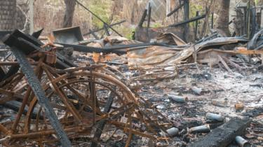 A rusted bicycle frame is seen amid the charred ruins of a Muslim village