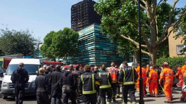 Firefighters at Grenfeell Tower after a minute's silence on Monday