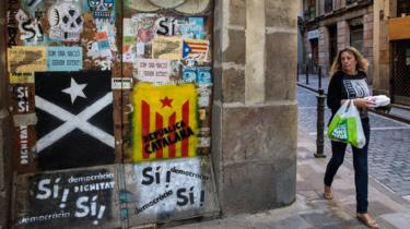 A woman walks past pieces of Catalan pro-independence graffiti on some doors in Barcelona